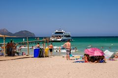 Ankomst för skepp för turistklockakryssning på den Playa de Muro stranden i den Alcudia fjärden Royaltyfri Foto