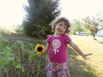 Anlage des kleinen Mädchens und der Sonnenblume draußen stockbild