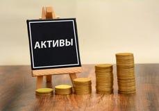 Anlagegüter fassen geschrieben auf russisch zusammen mit Währungsmünzenstapel ab Lizenzfreies Stockbild