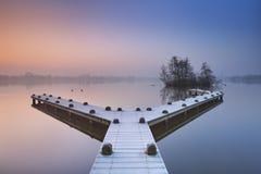 Anlegestelle auf einem ruhigen See auf dem Morgen eines nebeligen Winters Stockfotos