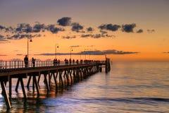 Anlegestelle mit Leuteschattenbild während des Sonnenuntergangs Lizenzfreies Stockfoto