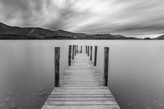Anlegestelle am See mit schwermütigem Himmel Stockfotografie