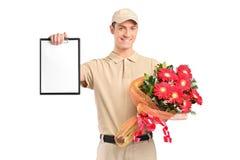 Anlieferungsjunge, der einen Blumenstrauß der Blumen anhält Stockfotografie