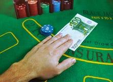 Anmärkning för euro 100 som utbyts för dobbelchiper på en grön filtblackjacktabell på kasinot Royaltyfri Bild