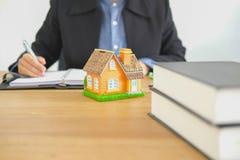 anmärkning för fastighetsmäklarefastighetsmäklarehandstil med husmodellen buying royaltyfri fotografi
