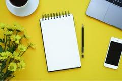 Anmärkning på gul bakgrund med telefonen, blommor, kaffe och bärbara datorn kopiera avstånd royaltyfria bilder