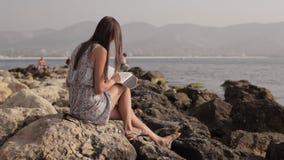 Anmärkningar för Yong kvinnadanande i dagbok på stranden stock video
