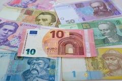 Anmärkningen av 10 euro ligger över de ukrainska pappers- pengarna, en bakgrund Royaltyfri Bild