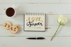 Anmärkningen för hälsningen för bokstäver för handen för dagen för valentin` s med te, kakor och steg Arkivbilder