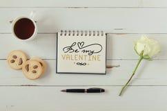 Anmärkningen för hälsningen för bokstäver för handen för dagen för valentin` s med te, kakor och steg Arkivfoton