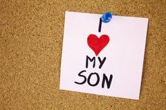 Anmärkningen med älskar jag min son Anmärkningen med älskar jag min son och röda hjärta på korkbrädebakgrund Arkivbild