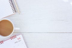 Anmärkningsbok för bästa sikt, kalender och kaffekopp på vit trätabl royaltyfri bild