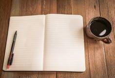 Anmärkningsbok och kaffekopp på träbakgrund Royaltyfria Bilder