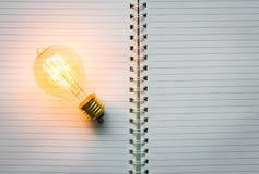 Anmärkningsbok och ljus kula på bakgrund Arkivbilder