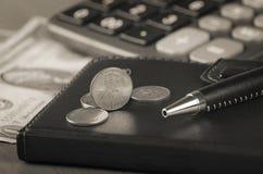 Anmärkningsbok och mynt Arkivbilder