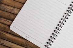 Anmärkningsbok på en bambubakgrund, enkel textur Fotografering för Bildbyråer