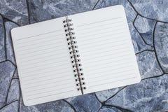 Anmärkningsbok på en stenbakgrund, enkel textur Arkivfoto
