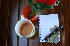 anmärkningsbok, penna, mynt, en kopp av varmt te och garnering för röda rosor som isoleras på träbakgrund Fotografering för Bildbyråer