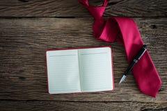 Anmärkningsbok, penna, röd slips på grungy träyttersida Royaltyfri Bild
