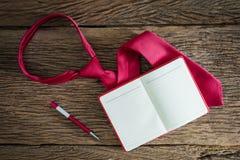 Anmärkningsbok, penna, röd slips på grungy träyttersida Fotografering för Bildbyråer