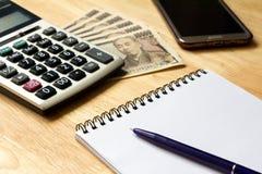 Anmärkningsboken med pennan, räknemaskin, ilar telefonen, sedel för japansk yen Arkivbilder