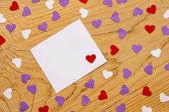 Anmärkningspapper och hjärtor på träbakgrund royaltyfri fotografi
