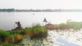 Anmärkningsvärd ssunset med fiskare vid floden lager videofilmer