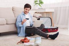 Anmeldung etikettiert online Mann, der für Ferien, unter Verwendung des Laptops sich vorbereitet lizenzfreies stockfoto
