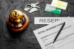 Anmeldungsform für Hotelzimmerreservierung, Stift und Ringdunkelheit backg lizenzfreie stockfotos