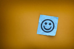 Anmerkung des blauen Papiers mit glücklichem Gesicht auf einem gelben Papierhintergrund Lizenzfreie Stockbilder