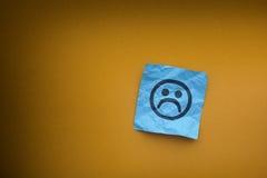 Anmerkung des blauen Papiers mit traurigem Gesicht auf einem gelben Papierhintergrund Stockfotografie