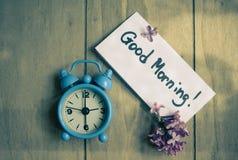 Anmerkung des gutenmorgens und alt-angeredete Uhr Stockfotografie