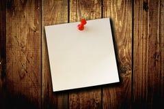 Anmerkung des leeren Papiers über hölzernen Bretthintergrund Lizenzfreies Stockfoto