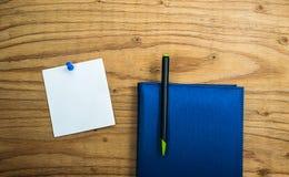 Anmerkung des leeren Papiers über hölzernen Hintergrund mit blauem Stift und Tagebuch buchen Stockbild