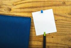 Anmerkung des leeren Papiers über hölzernen Hintergrund mit blauem Stift und Tagebuch buchen stockfoto