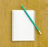 Anmerkung und Bleistift auf hölzernem Lizenzfreies Stockbild