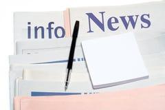 Anmerkung und Feder, über gestapelten Zeitungen Lizenzfreie Stockfotos