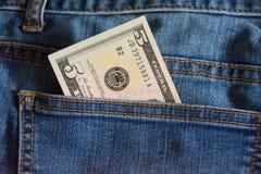 Anmerkung von fünf Dollar in den Jeans stecken ein Stockbilder
