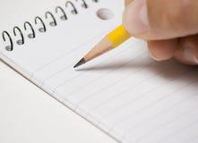 Anmerkungs-Auflage mit Bleistift in der Hand Stockfotos
