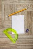 Anmerkungsbuch-, Bleistift- und Winkelmessermachthaber auf einer hölzernen Beschaffenheit Stockbild