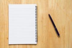 Anmerkungsbuch des leeren Papiers mit Stift auf hölzerner Tabelle Lizenzfreie Stockfotos