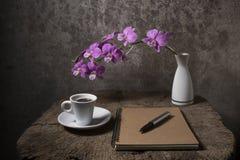 Anmerkungsbuch leer mit Kaffeetasse und purpurroter Orchidee im Vase auf Stockbild