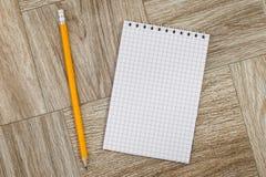 Anmerkungsbuch mit Bleistift auf einer hölzernen Beschaffenheit Stockfotos
