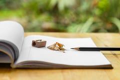 Anmerkungsbuch mit Bleistift, Bleistiftspitzer und Schnitzeln Stockbild
