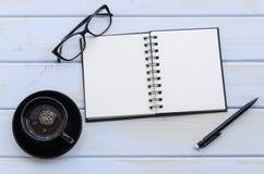 Anmerkungsbuch mit Bleistift, Gläsern und einer Schale coffie auf einem hölzernen Schreibtisch Stockbild