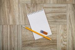 Anmerkungsbuch mit Bleistift und Radiergummi auf einer hölzernen Beschaffenheit Stockfotos