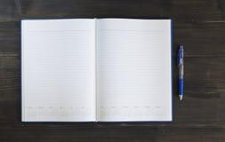 Anmerkungsbuch mit Stift auf dem hölzernen Hintergrund Lizenzfreies Stockbild