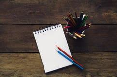 Anmerkungsbuch- und -bleistiftfarben auf hölzernem Lizenzfreies Stockfoto
