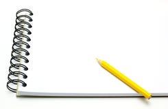 Anmerkungsbuch und gelber Bleistift, getrennt auf Weiß Stockfotografie