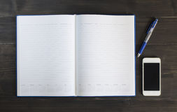 Anmerkungsbuch und intelligentes Telefon auf dem hölzernen Hintergrund Stockbilder
